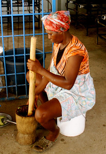 A woman uses a mortar and pestle.