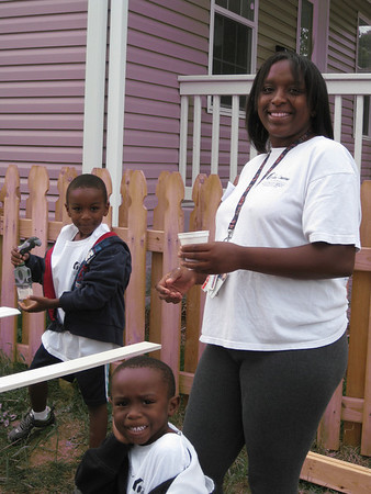 Fuller Center homeowner Ms. Parker and her sons help out.
