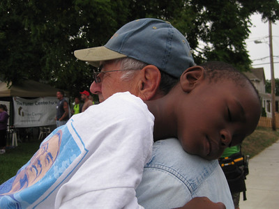 Early on Day 1, Ron Fisher holds a sleeping Kamarie, who lives in one of the Fuller Center homes built during the 2010 Millard Fuller Legacy Build and who was on hand this week to help serve water to volunteers on the September 2011 build.