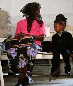 A Haitian woman and boy listen to Bishop Jeune's sermon.