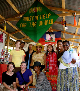 """The all-women's team poses for a picture underneath the """"House of Help for the Women"""" banner."""