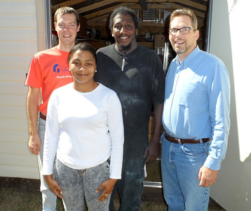 Americus-Sumter Fuller Center Director Brett Saffran, left, and Director of U.S. Field Operations Kirk Lyman-Barner pose with the future Toolie Build homeowners — Damien Battle and Cassie Wilcher, parents of three children ages 7, 6 and 4. They are engaged to be married in March 2014.