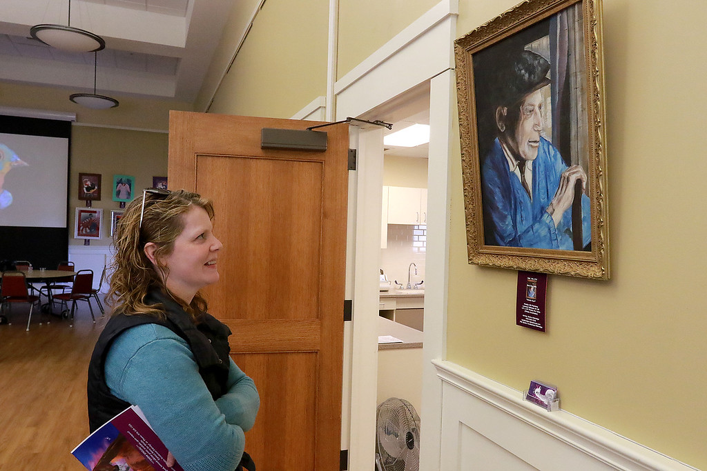 ". Paintings and photography by legally blind artist Bette Avadanian Eldredge where on display at the Townsend Meeting Hall on Saturday, April 6, 2019. Eldredge\'s friend Karen McNabb-Noon looks over her piece called ""Uncle Kar.\"" SENTINEL & ENTERPRISE/JOHN LOVE"