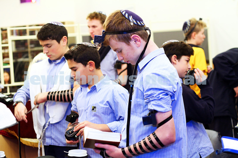 15-7-15. Students at Leibler-Yavneh College put on tefillin during their morning prayers. The service is lead by Rabbi Noam Sendor. Photo: Peter Haskin