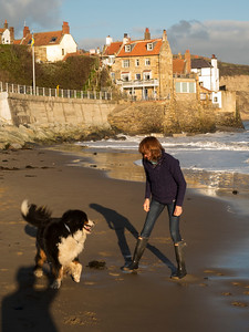 woman with dog on Robin Hoods Bay beach, Norh Yorkshire coast