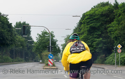 Gelsenkirchen, Germany - June 25, 2005: Mature woman cycling on a multiple lane highway in Gelsenkirchen, Germany. She wears a rain jacket, shorts and a cycling helmet.
