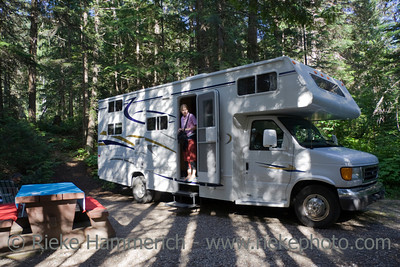 Big Motorhome at a wooded campground with young woman - Highway 18 in British Columbia, Canada