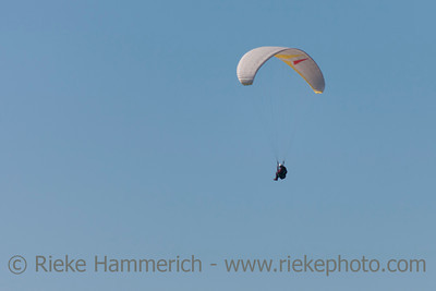 Paraglider against blue sky