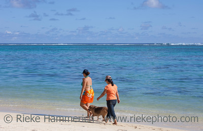 Women walking the Dog on tropical Beach - Rarotonga, Cook Islands, Polynesia