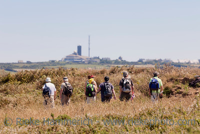 Jobourg, France - July 3, 2011:Hikers with backpack on the Nez of Jobourg, France. They look at the nuclear fuel reprocessing plant of La Hague, which is located in a rural landscape.