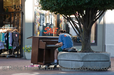 Victoria, British Columbia, Canada – August 2, 2005: Street Musician playing piano in front of a clothing store in the pedestrian zone of Victoria, Canada.