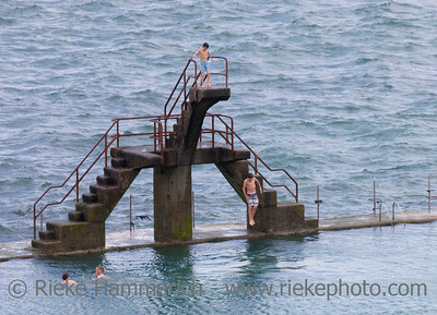 SAINT-MALO, FRANCE - JULY 6: Teenage boy jumping into seawater pool in Saint-Malo, France on July 6, 2011. Another boy is watching him from the diving board, two young men are swimming in the pool.