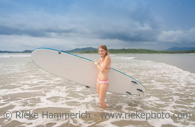 Young woman with surfboard on beach - Playa Grande, Tamarindo, Guanacaste Province, Costa Rica
