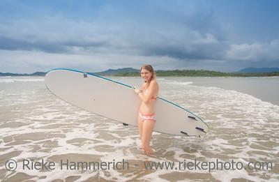 Young woman with surfboard on beach - Playa Grande, Tamarindo, Guanacaste Province, Costa Rica