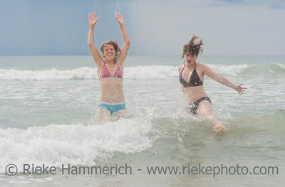 TAMARINDO, COSTA RICA - SEPTEMBER 13: Young women jumping in waves on the beach inTamarindo, Costa Rica on September 13, 2008. Tamarindo is located on the Northern Pacific Coast.