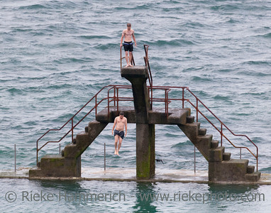 SAINT-MALO, FRANCE - JULY 6: Young man jumping into seawater pool in Saint-Malo, France on July 6, 2011. Another man is waiting on the diving platform.
