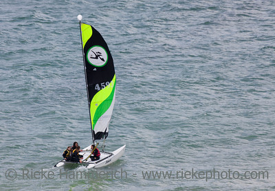 SAINT-MALO, FRANCE - JULY 6: Four teenage girls catamaran sailing on the coast of Saint-Malo, France on July 6, 2011. Their Hobie Cat 15 catamaran is 15 feet long and has a great buoyancy.