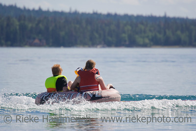 Girl and boy pulled in rubber dinghy - Green Lake, South Cariboo, British Columbia, Canada