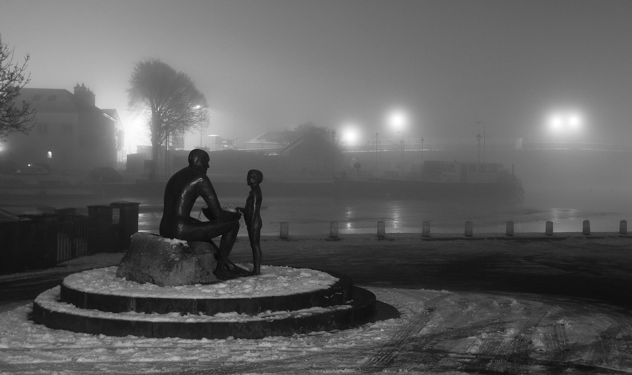 The Man & Boy statue in Carrick-on-Shannon in Co. Leitrim, Ireland. The photograph was taken during the winter of 2009 (Christmas Eve) when most of Ireland was covered in snow. In the background, obscured by the icy fog,is a river boat and also the bridge that spans the river Shannon which marks the boundary between counties Leitrim and Roscommon.