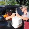 Men's Club member Danny Houghton delivers fish meals to parishioner Lynn Eschete. (NTC photo/Donna Ryckaert)