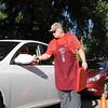 St. Vincent de Paul Men's Club member Tom Wallace collects payment from a drive-thru customer. (NTC photo/Donna Ryckaert)