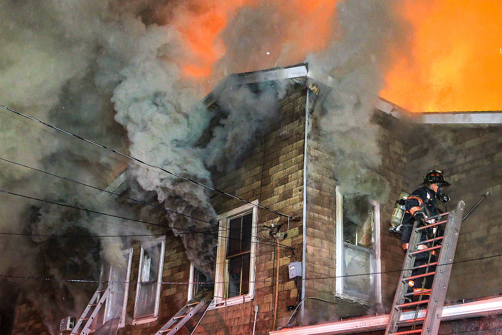 . Leominster firefighters work to contain a two-alarm fire that sweep through a Lincoln Terrace multi-family dwelling early Tuesday morning. SENTINEL & ENTERPRISE/SCOTT LAPRADE