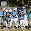 Leominster American,  bark blue shirts, played Leominster National on Friday night at Angelo Picucci Field in Leominster. Leominster National players surround home plate as the congratulate their teammate Tom Gosson on his home run hit during action in the game. SENTINEL & ENTERPRISE/JOHN LOVE