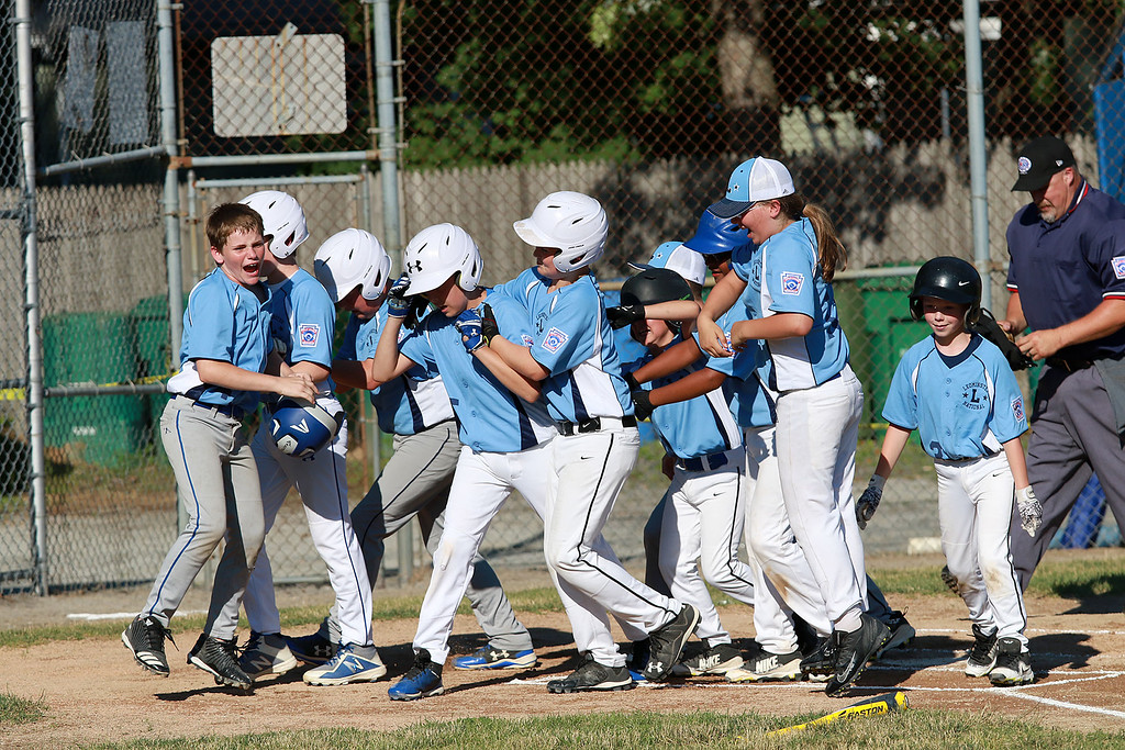 . Leominster American,  bark blue shirts, played Leominster National on Friday night at Angelo Picucci Field in Leominster. Leominster National players surround home plate as the congratulate their teammate Tom Gosson on his home run hit during action in the game. SENTINEL & ENTERPRISE/JOHN LOVE