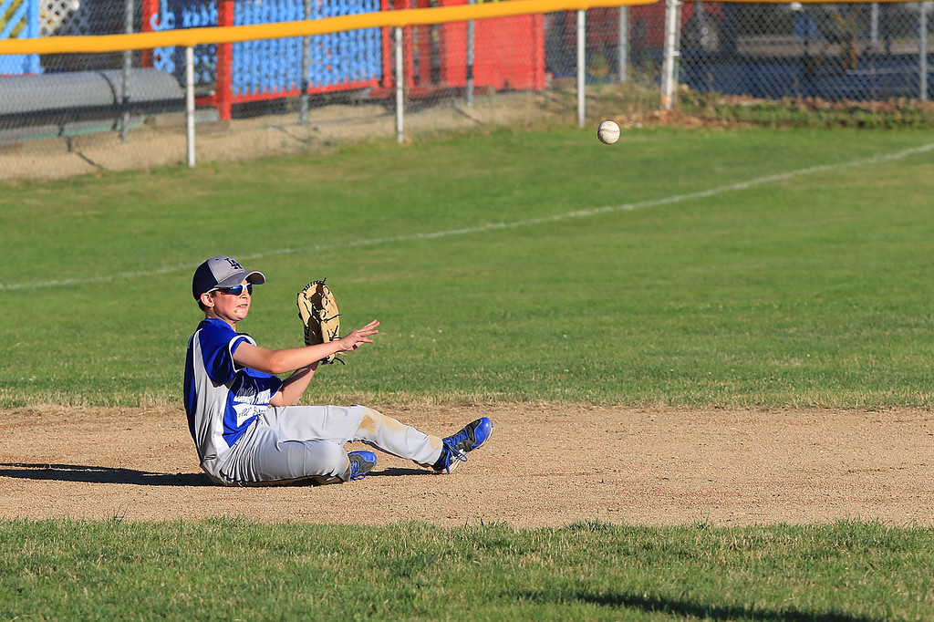 . Leominster American, bark blue shirts, played Leominster National on Friday night at Angelo Picucci Field in Leominster. Leominster American player Louis Ciccolini makes a nice throw from a seated position to make an out at second after diving for a ground ball.  SENTINEL & ENTERPRISE/JOHN LOVE