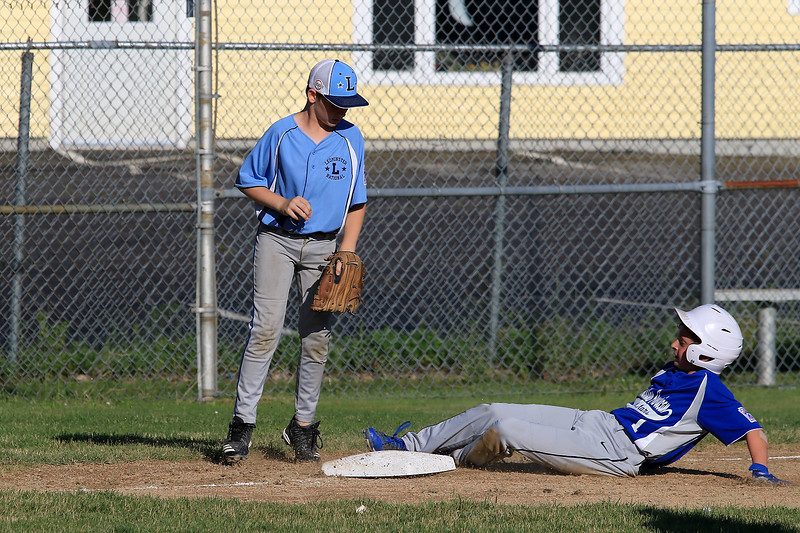 Leominster American, bark blue shirts, played Leominster National on Friday night at Angelo Picucci Field in Leominster. Leominster National player Jack Forgues watches as Leominster American player Louis Ciccolini slides safe into third base. SENTINEL & ENTERPRISE/JOHN LOVE