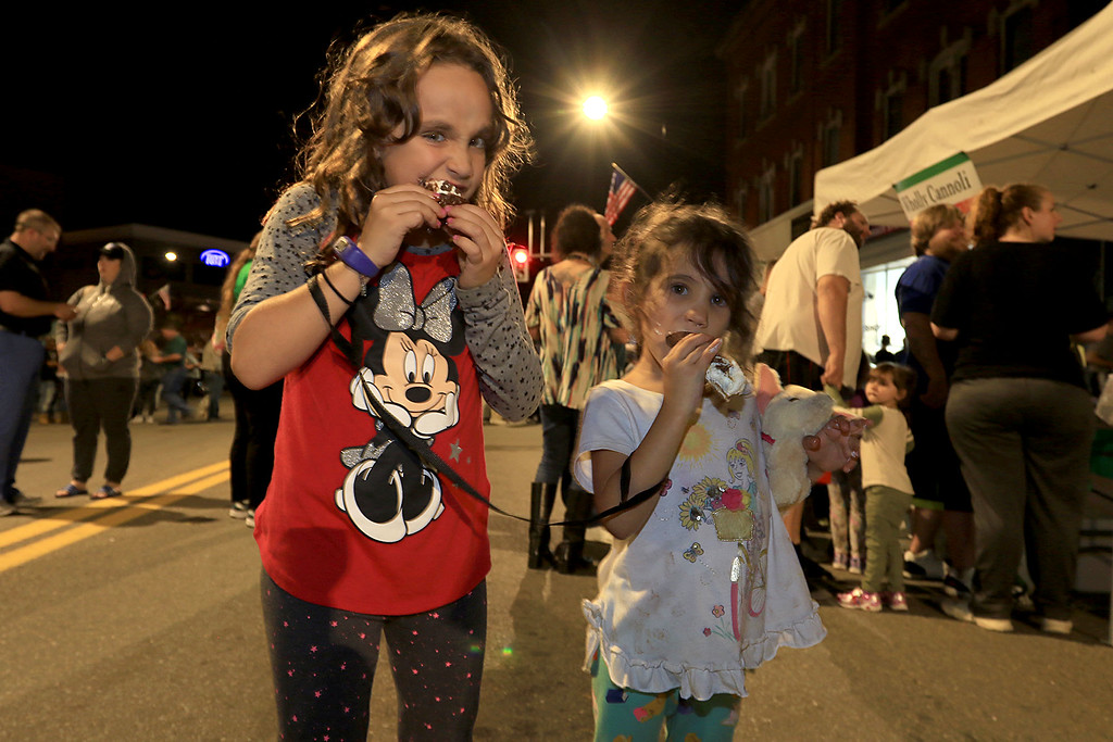 . Trying some cannoli\'s at Leominster\'s Cannoli Festival on Thursday night, October 4, 2018 is sisters Amalia Monteverde, 7, and Isabella Monteverede. 5, of Lancaster. SENTINEL & ENTERPRISE/JOHN LOVE