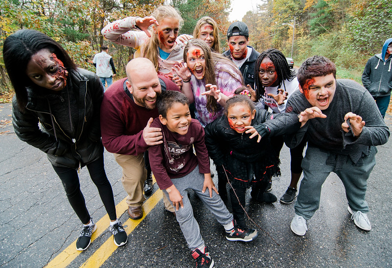 """Evan Feeley, 6, and dad Chris get a scare from the Leominster High """"zombies"""" during the Running Dead 5K on Saturday afternoon. The Class of 2018 held the event in hopes of reaching their target revenue goal of $2,000. The money will be used to help cover graduation, prom and class gift costs. SENTINEL & ENTERPRISE / Ashley Green"""