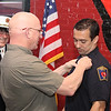 Chief Robert Sideleau watches as Ret Ff and Father Steve Augat pin's a Lieutenant's badge on his son Seth Augat