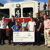 "Joshua and Brandon Mills, holding a check with sister MacKenzie, have the Becker form of muscular dystrophy. They were recently in Leominster when the Fire Department presented $8,189, the proceeds from its annual ""boot shake"" for the Muscular Dystrophy Association. Joining Joshua, Brandon and MacKenzie are, from left, Fire Chief Robert Sideleau II, firefighter Matt Burke, Sherri Mill, the children's mother, firefighter Ben Brideau, and MDA coordinator Will Southall.<br /> SENTINEL & ENTERPRISE / SCOTT LAPRADE"