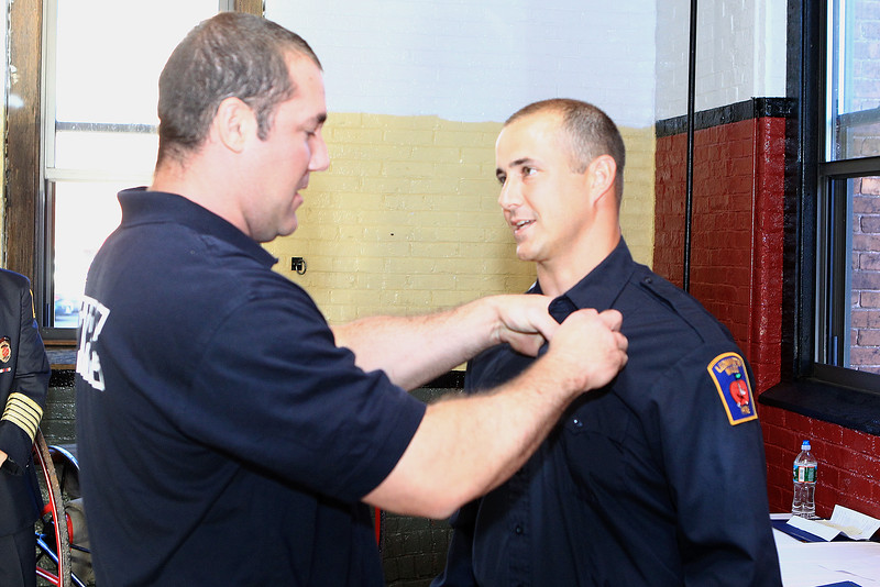 Ff Sean Gray pins FF Tim Comeau's badge on