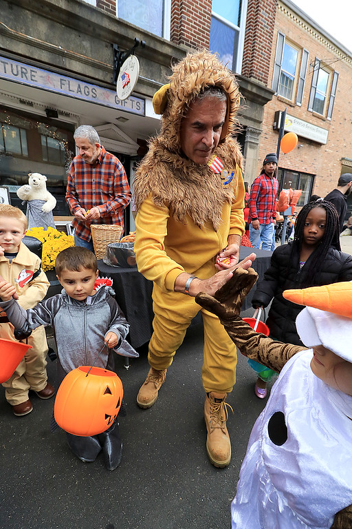 . The annual Halloween parade in Leominster was held on Saturday, October 20, 2018 in down town around Monument Square. The business were handing out candy to all the kids and the common was cover in tables with many politicians. Leominster Mayor Dean Mazzarella dessed as the lion from the Wizard of OZ high fives Isabella Rounds, 4, of Leominster dressed as Olaf from Frozen as he handed out candy during the event. SENTINEL & ENTERPRISE/JOHN LOVE