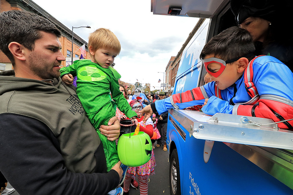 . The annual Halloween parade in Leominster was held on Saturday, October 20, 2018 in down town around Monument Square. The business were handing out candy to all the kids and the common was cover in tables with many politicians. Mitch Mills holds his son Alexander, 3, as he gets candy from Gabriel Vargas, 7, in the Fidelity Bank\'s Frosty Flyer van during the event. Alexander was dressed up as Gekko from the the Disney show P.J. Masks. SENTINEL & ENTERPRISE/JOHN LOVE