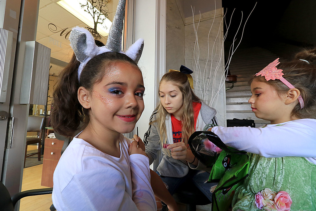 . The annual Halloween parade in Leominster was held on Saturday, October 20, 2018 in down town around Monument Square. The business were handing out candy to all the kids and the common was cover in tables with many politicians. St. Bernard\'s Catholic High School cheerleader Mia Dondero, 15, puts a sparkly tattoo on to Mya PanIagua, 7, of Leominser dressed as a Unicorn. Watching them is Ava Maldonado, 5, of Fitchburg waiting her turn. SENTINEL & ENTERPRISE/JOHN LOVE