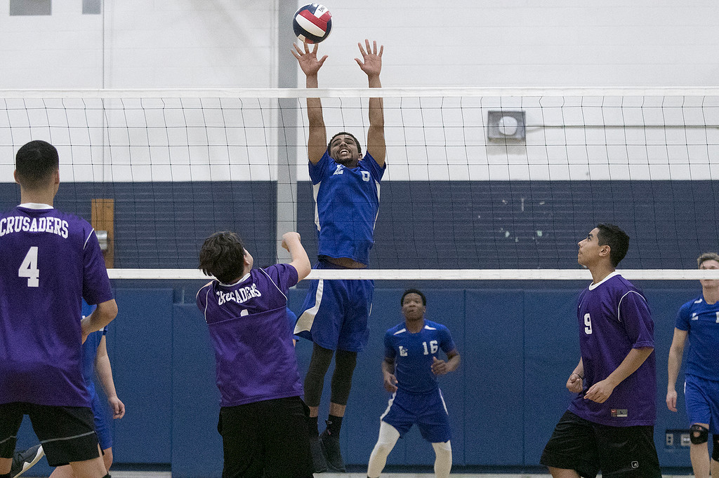 . Leominster High School volleyball player Andrews Annan leaps to block the ball during action in the match. SENTINEL & ENTERPRISE/JOHN LOVE