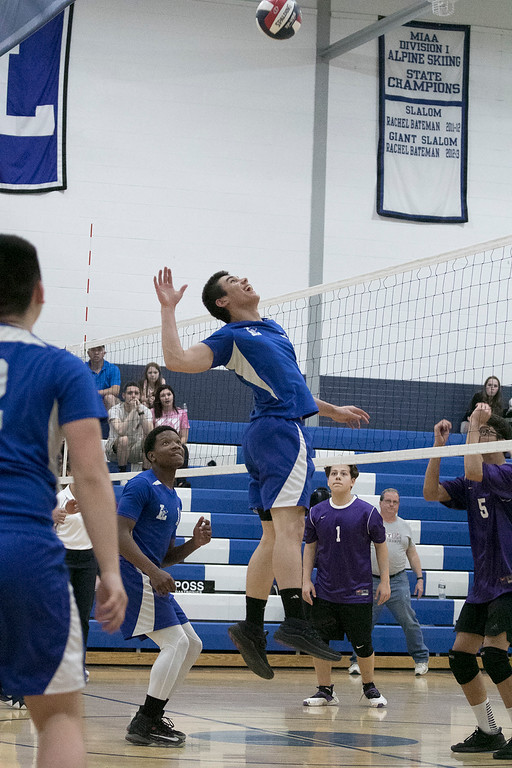 . Leominster High School volleyball player Eric Jenny leaps to hit the ball over the net. SENTINEL & ENTERPRISE/JOHN LOVE