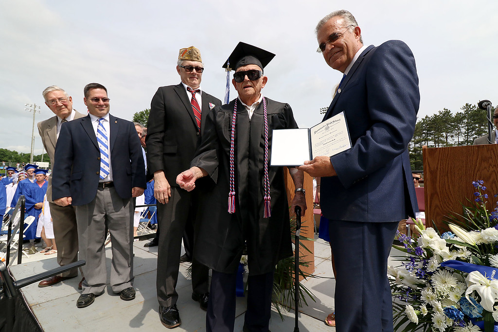 . Leominster high School class of 2018 held their 148th commencement on Saturday, June 2, 2018. Mayor Dean Mazzarella, on right, gives WWII veteran Roland Martineau, 94, his well overdue Leominster High School diploma at the start of the ceremony. Just behind Martineau is City Councilor Frank Ardinger,  Director of Veterans Services for Leominster Rick Voutour and Army retired Master Sgt. Dennis Lyddy. SENTINEL & ENTERPRISE/JOHN LOVE