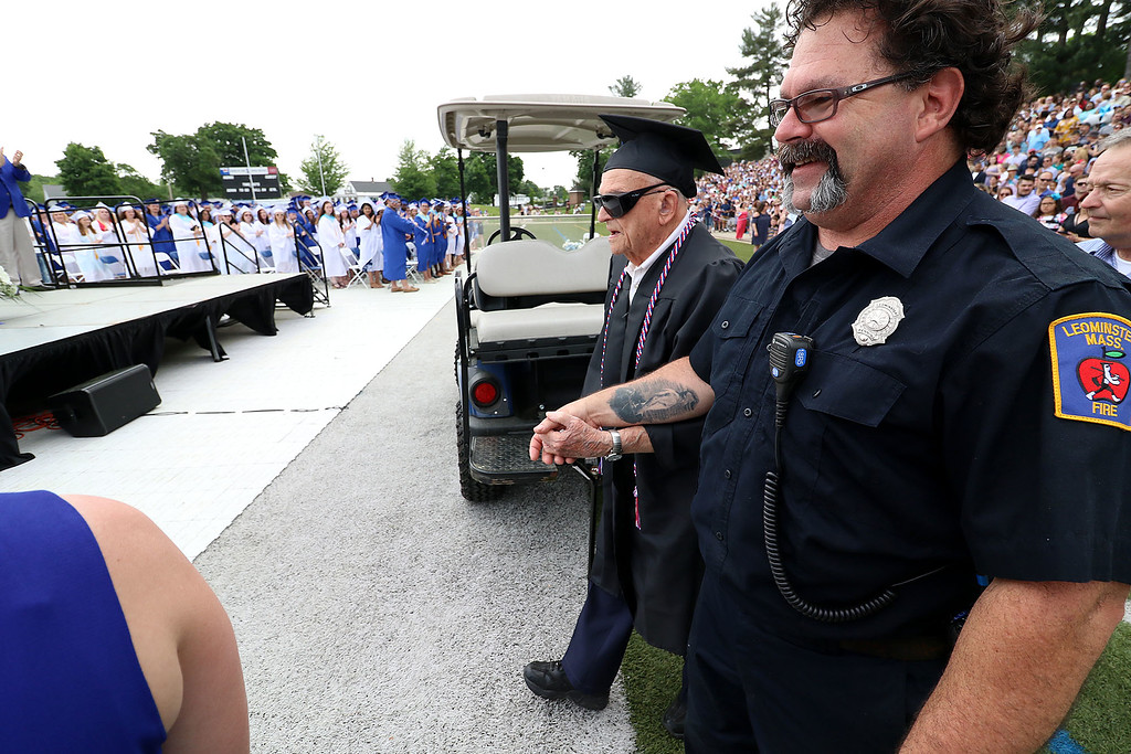 . Leominster high School class of 2018 held their 148th commencement on Saturday, June 2, 2018. Roland Martineau, 94, makes his way onto the football field with the help of Firefighter Bob Penning to finally receive his 1942 high school diploma. SENTINEL & ENTERPRISE/JOHN LOVE