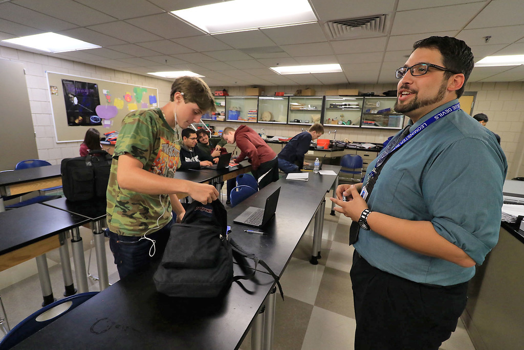 . Leominster High School Principals of Technology teacher Carlos Silva, 29, in his classroom on Thursday, September 20, 2018. He became a United States citizen on Wednesday in a ceremony in Lowell. He moved to Leominster with his family when he was very young. He is also a graduate of LHS. he tells his students what is due for tomorrow\'s class as they pack up to go to lunch. SENTINEL & ENTERPRISE/JOHN LOVE