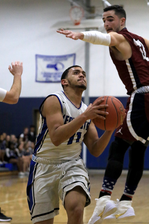 . Leominster High School basketball played Westborough High School on Tuesday night at home. LHS\'s Eduardo Flores Ramierez makes his way past WHS\'s William Collins as he drives to the basket. SENTINEL & ENTERPRISE/JOHN LOVE