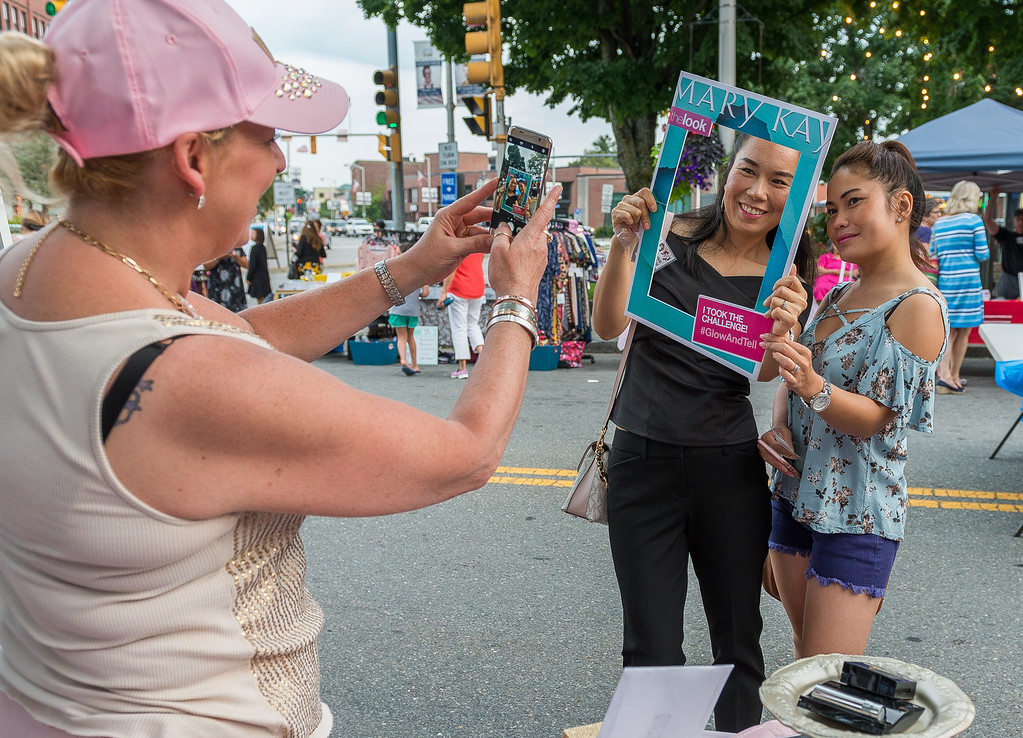 . Michelle Morin snaps a picture of Soneamaly Phetsirreseng and Sysanga Saignaphone during Ladies Night Out in Leominster. SENTINEL&ENTERPRISE/ Jim Marabello