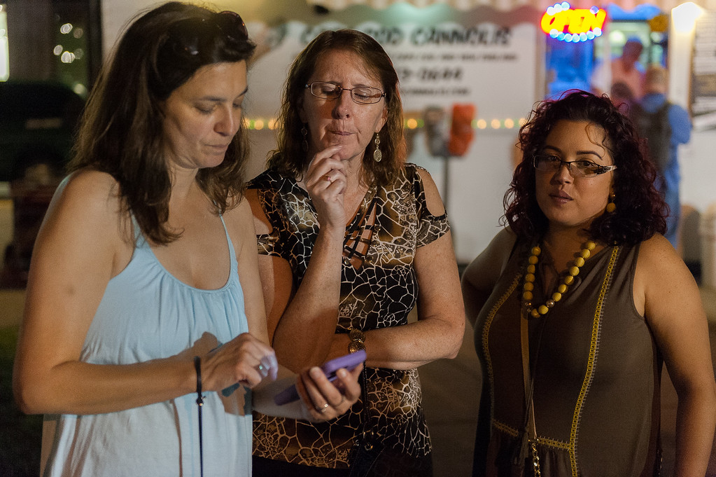 . Michelle Contey, Amy LaBarge and Viviana Martinez check out photos of the Ladies Night Out Fashion Show which featured local models, fashions makeup and hair. SENTINEL&ENTERPRISE/ Jim Marabello