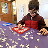 Brothers Ilan, 9, Erez, 7, and Oren Cohen, 16, worked on a Color-Me Puzzle at the Leominster Public Library on Thursday morning, December 27, 2018 during the library program. Oren looks over his pieces as he works to put the puzzle together with his brothers. Ilan works on the edge of the puzzle as he and his brothers work to put together the puzzle. SENTINEL & ENTERPRISE/JOHN LOVE