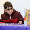 Brothers Ilan, 9, Erez, 7, and Oren Cohen, 16, worked on a Color-Me Puzzle at the Leominster Public Library on Thursday morning, December 27, 2018 during the library program. Oren looks over his pieces as he works to put the puzzle together with his brothers. Ilan uses the puzzle box picture to help him put together the puzzle with his brothers. SENTINEL & ENTERPRISE/JOHN LOVE