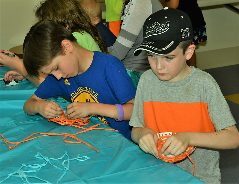 Michael Thompson (left) and Michael Gibbons were concentrating on weaving a basket during a program at the Leominster Public Library Monday afternoon.<br /> Sentinel & Enterprise / Jim Fay