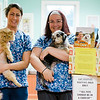 Staff members Caelyn Colello, along with clinic pet Pogo, and Michelle Kelley, with clinic pet Amy, show off the collection of food for the annual Pet Holiday Drive at Central Animal Hospital in Leominster. SENTINEL & ENTERPRISE / Ashley Green